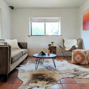 他の地域の小さいサンタフェスタイルのおしゃれな独立型リビング (白い壁、テラコッタタイルの床、コーナー設置型暖炉、漆喰の暖炉まわり、テレビなし、オレンジの床) の写真