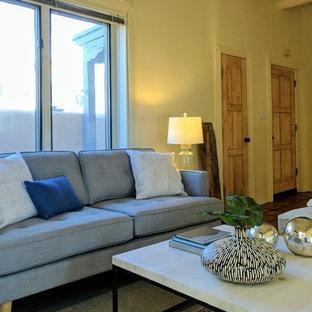 アルバカーキの小さいサンタフェスタイルのおしゃれなLDK (黄色い壁、テラコッタタイルの床、コーナー設置型暖炉、漆喰の暖炉まわり、テレビなし) の写真