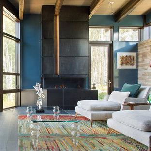 Idéer för att renovera ett funkis vardagsrum, med blå väggar, en bred öppen spis, en spiselkrans i metall, ett finrum och mörkt trägolv