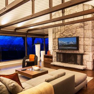 Esempio di un grande soggiorno minimal stile loft con pavimento in legno massello medio, camino lineare Ribbon, cornice del camino in pietra e TV a parete