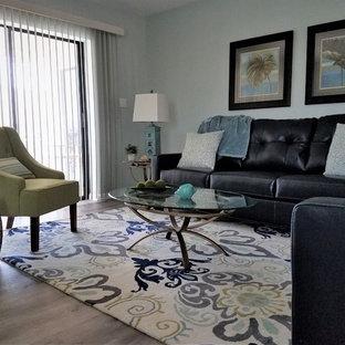 他の地域の中サイズのビーチスタイルのおしゃれなLDK (青い壁、クッションフロア、暖炉なし、壁掛け型テレビ、グレーの床) の写真