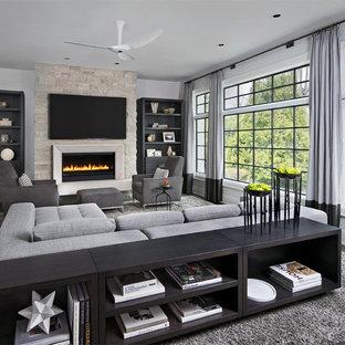 Foto di un grande soggiorno minimal aperto con pareti grigie, pavimento in legno massello medio, camino classico, cornice del camino in pietra e TV a parete