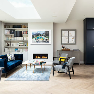 This is an example of a contemporary open plan living room in London with a reading nook, grey walls, light hardwood flooring, a ribbon fireplace and no tv.