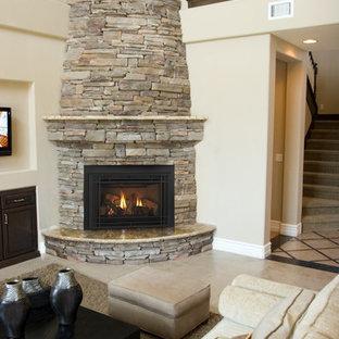 リトルロックの中サイズのトラディショナルスタイルのおしゃれなLDK (フォーマル、黄色い壁、トラバーチンの床、吊り下げ式暖炉、石材の暖炉まわり、テレビなし、ベージュの床) の写真