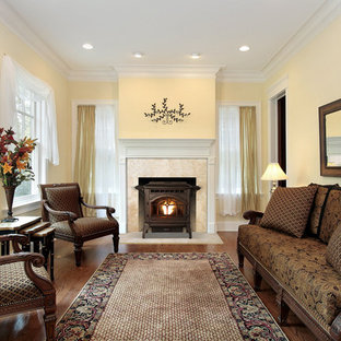 Traditional formal enclosed living room in Other with yellow walls, medium hardwood floors, a wood stove, a metal fireplace surround and brown floor.