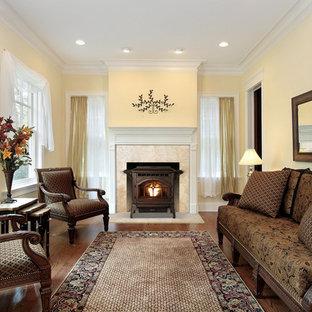 Modelo de salón para visitas cerrado, clásico, con paredes amarillas, suelo de madera en tonos medios, estufa de leña, marco de chimenea de metal y suelo marrón