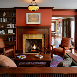 Example of an arts and crafts enclosed medium tone wood floor living room library design in Seattle with red walls, a standard fireplace, a tile fireplace and no tv