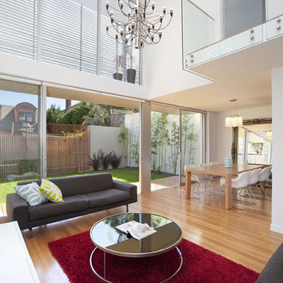 Large trendy open concept light wood floor living room photo in Sydney with white walls