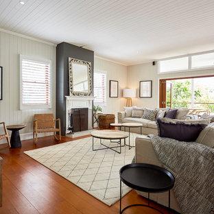 Idee per un soggiorno tropicale di medie dimensioni e aperto con pareti bianche, parquet chiaro, camino classico, cornice del camino in intonaco e pavimento marrone