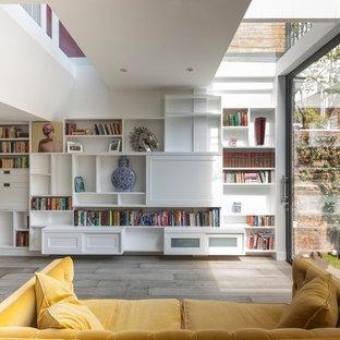 Cette image montre un grand salon nordique ouvert avec une salle de réception, un mur blanc, un téléviseur dissimulé, un sol en bois clair, une cheminée standard et un manteau de cheminée en pierre.