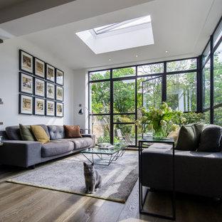 Immagine di un soggiorno contemporaneo di medie dimensioni e aperto con parete attrezzata, pareti bianche, pavimento in legno massello medio e pavimento marrone