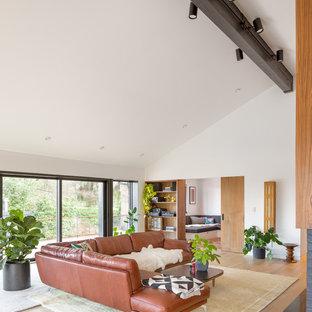 Diseño de biblioteca en casa abierta, retro, de tamaño medio, con paredes blancas, suelo de madera clara, chimenea tradicional y marco de chimenea de madera