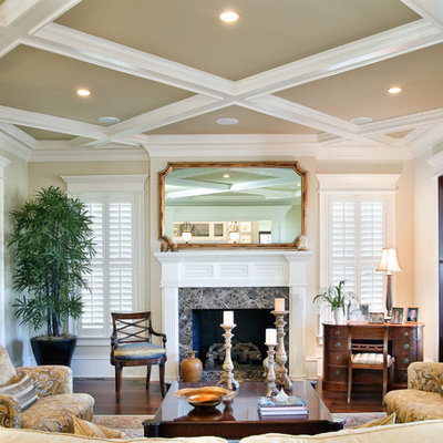 Example of a large classic formal and enclosed dark wood floor living room design in Charleston with beige walls, a standard fireplace and no tv