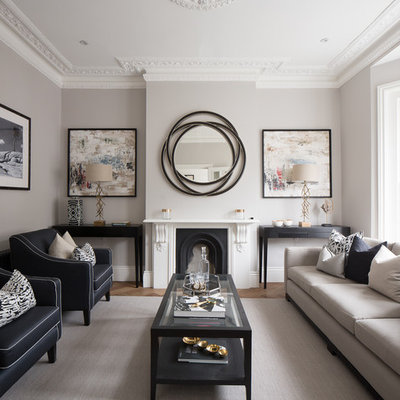 Transitional formal medium tone wood floor living room photo in London with gray walls, a standard fireplace and no tv