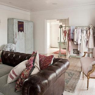 Cette image montre un salon style shabby chic de taille moyenne et fermé avec un mur blanc et un sol en bois clair.