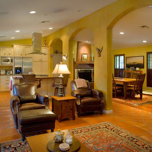 ヒューストンの大きいラスティックスタイルのおしゃれなLDK (黄色い壁、テラコッタタイルの床、暖炉なし、埋込式メディアウォール) の写真
