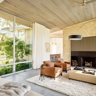 Foto de salón para visitas actual con suelo de cemento y chimenea tradicional