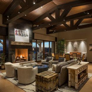 Immagine di un grande soggiorno american style aperto con pareti beige, pavimento in cemento, camino classico, cornice del camino in metallo e TV a parete