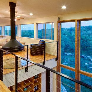 Foto di un soggiorno minimal stile loft con camino sospeso, pareti beige, pavimento in legno massello medio e nessuna TV
