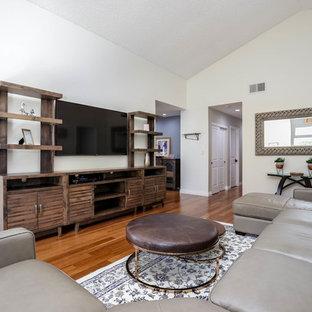 Immagine di un ampio soggiorno minimal aperto con sala formale, pareti bianche, pavimento in bambù, camino classico, cornice del camino in mattoni e TV a parete