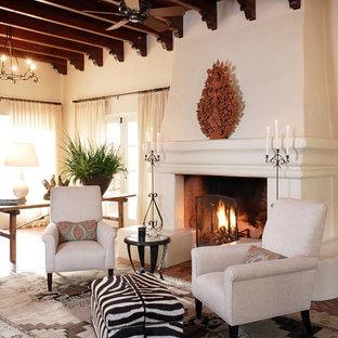 サンディエゴの広い地中海スタイルのおしゃれなLDK (フォーマル、白い壁、テレビなし、テラコッタタイルの床、標準型暖炉、漆喰の暖炉まわり、マルチカラーの床) の写真