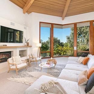 Offenes Modernes Wohnzimmer mit weißer Wandfarbe, Teppichboden, Kamin, Wand-TV, grauem Boden, freigelegten Dachbalken, gewölbter Decke und Holzdecke in San Diego
