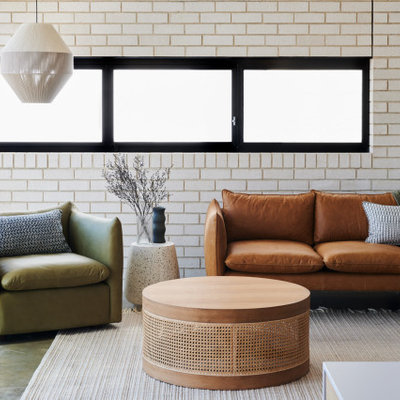 Mid-sized trendy open concept concrete floor and gray floor living room photo in Adelaide with white walls and a wall-mounted tv