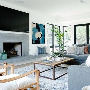 Immagine di un grande soggiorno design aperto con pareti bianche, camino classico, cornice del camino in cemento, TV a parete, parquet chiaro e pavimento grigio