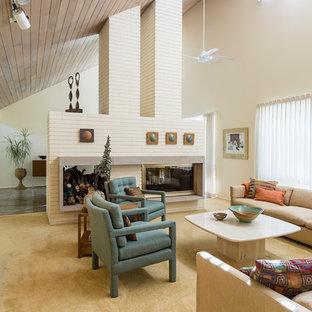 Immagine di un grande soggiorno moderno aperto con pareti bianche, moquette, camino bifacciale, cornice del camino in mattoni, sala formale e pavimento beige