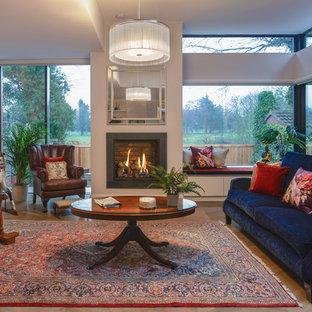 ダブリンの広いトランジショナルスタイルのおしゃれなLDK (グレーの壁、淡色無垢フローリング、吊り下げ式暖炉、金属の暖炉まわり、内蔵型テレビ) の写真