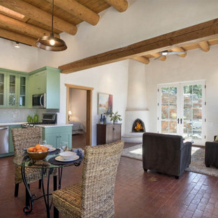 Contemporary open concept living room in Albuquerque with white walls, brick floors, a corner fireplace, a plaster fireplace surround and red floor.