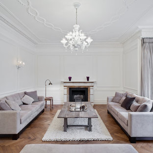 Photo of a classic formal living room in London with a standard fireplace, white walls, light hardwood flooring and a stone fireplace surround.