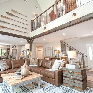 Ispirazione per un grande soggiorno stile americano aperto con pareti grigie, pavimento in legno massello medio, camino classico, cornice del camino in pietra, parete attrezzata e pavimento marrone