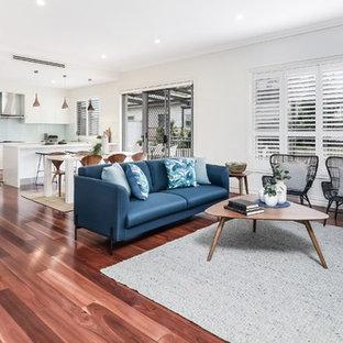 Idee per un soggiorno classico aperto con pareti beige, TV autoportante, pavimento rosso, pavimento in legno massello medio e nessun camino
