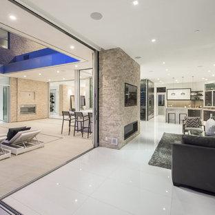 Inredning av ett modernt allrum med öppen planlösning, med vita väggar, laminatgolv, en bred öppen spis, en spiselkrans i sten, en väggmonterad TV och vitt golv