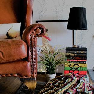 Esempio di un piccolo soggiorno minimal aperto con libreria, pareti grigie, parquet chiaro, stufa a legna, cornice del camino in cemento e nessuna TV