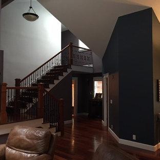 Esempio di un grande soggiorno american style aperto con pareti nere, parquet scuro, camino classico, cornice del camino piastrellata, TV autoportante e pavimento marrone