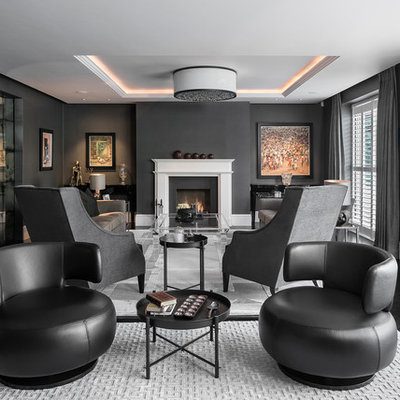 Example of a large trendy formal and enclosed dark wood floor and black floor living room design in Hampshire with black walls, a standard fireplace, a stone fireplace and no tv
