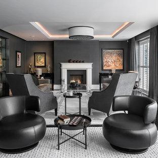 Foto de salón para visitas cerrado, actual, grande, sin televisor, con paredes negras, suelo de madera oscura, chimenea tradicional, marco de chimenea de piedra y suelo negro