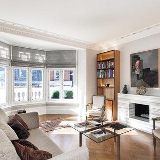 Foto de salón para visitas contemporáneo, de tamaño medio, con paredes beige, suelo de madera en tonos medios, chimenea tradicional, marco de chimenea de piedra y televisor colgado en la pared