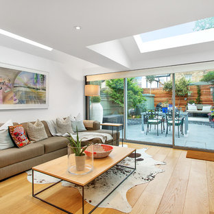 This is an example of a medium sized contemporary enclosed living room in London with white walls, light hardwood flooring, a freestanding tv and beige floors.