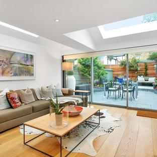 Idéer för ett mellanstort modernt separat vardagsrum, med vita väggar, ljust trägolv, en fristående TV och beiget golv