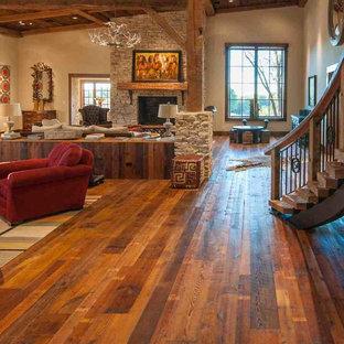 Ejemplo de salón para visitas abierto, rural, grande, con paredes beige, suelo de madera en tonos medios, estufa de leña, marco de chimenea de piedra y pared multimedia