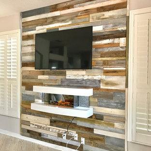 Ispirazione per un soggiorno minimalista di medie dimensioni e aperto con camino sospeso, cornice del camino in legno e pavimento grigio
