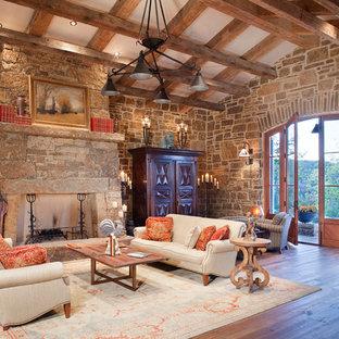 Aménagement d'un grand salon montagne fermé avec une salle de réception, un sol en bois foncé, un mur beige, une cheminée standard, un manteau de cheminée en pierre, un téléviseur dissimulé et un sol multicolore.