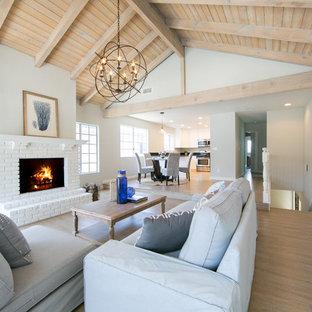 Idées déco pour un salon bord de mer avec un mur gris, un sol en bois brun, une cheminée standard et un manteau de cheminée en brique.