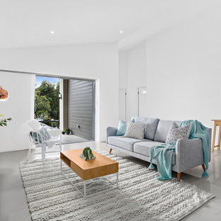 This is an example of a beach style living room in Other with white walls, a freestanding tv and grey floor.