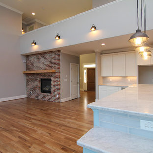 Large trendy open concept light wood floor living room photo in Raleigh with gray walls, a standard fireplace and a brick fireplace