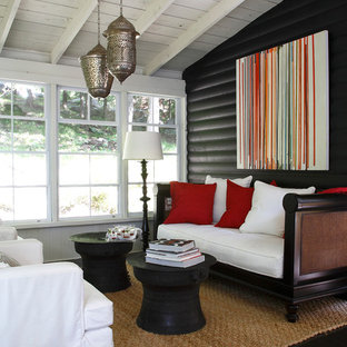 Example of a coastal black floor living room design in Other with black walls