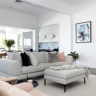 ブリスベンの広いコンテンポラリースタイルのおしゃれなLDK (白い壁、濃色無垢フローリング、塗装板張りの暖炉まわり、茶色い床、塗装板張りの壁) の写真